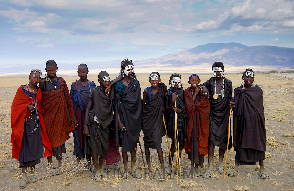 Young recently circumcised Masai Warriors (moran) with traditional face paint after 'coming of age',  and  young Masai girls,  in the Serengei Plains, Tanzania .