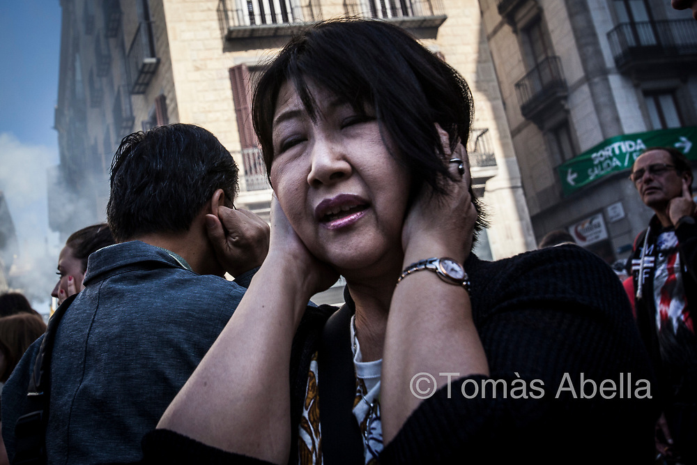 Tourist protecting her ears from the blast of blunderbusses fired at a popular street festivity. Sant Jaume Square.