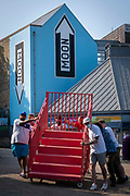 Preparing for the launch party of The Creative Folkestone Triennial 2020, The Plot, on the 21st of July 2021 in Folkestone, United Kingdom. Volunteers move some red stairs past the glassworks and the moon sign artwork. This is Folkestones 5th open air art exhibition and the third one curated by Lewis Biggs. The Plot sees 27 newly commissioned artworks appearing around the south coast seaside town. The new work builds on the work from previous triennials making Folkestone the biggest urban outdoor contemporary art exhibition in the UK.