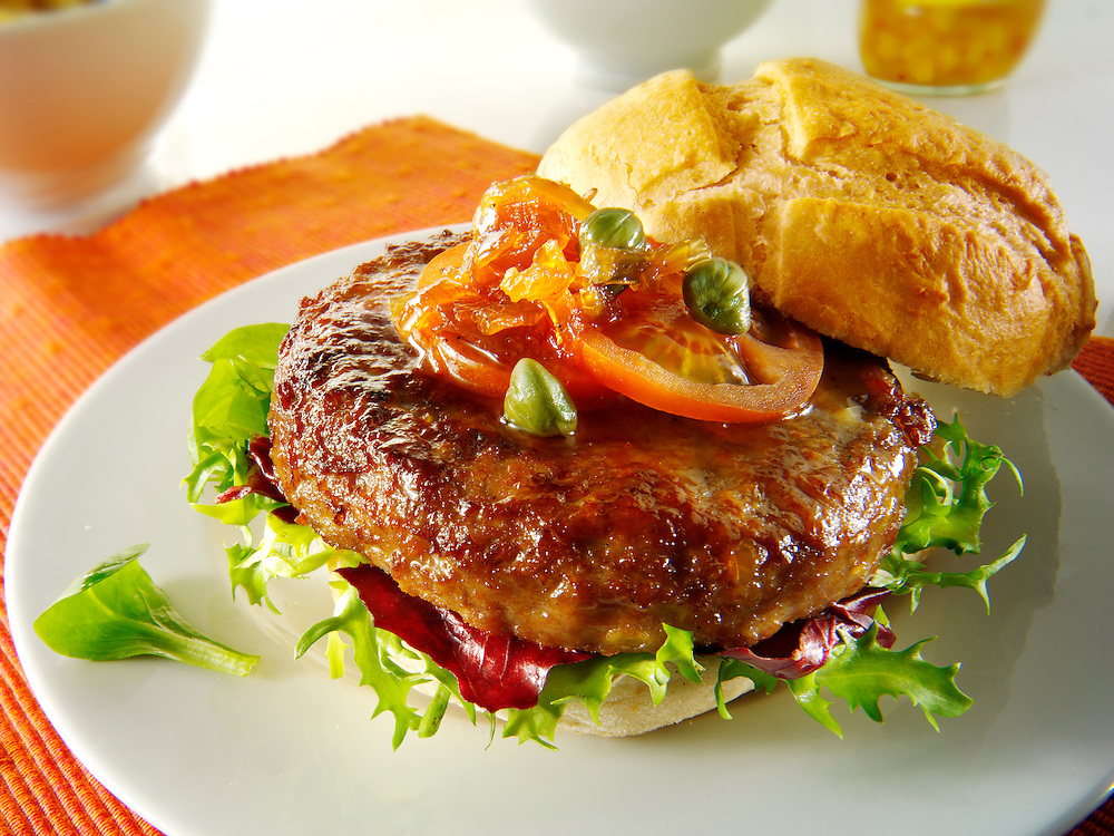 Organic beef burger with tomato relish and salad in a bun photo. Funky Stock Photos
