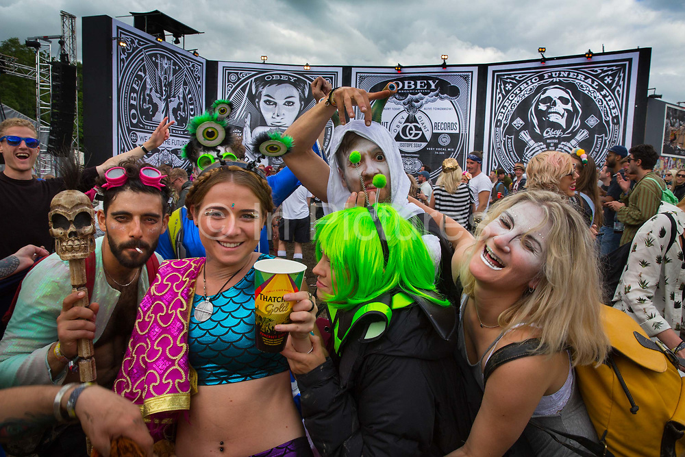 Group of aliens Dancing to Craig Charles at the Hell Stage, Shangri La field, Glastonbury Festival 2016. The Glastonbury Festival is the largest greenfield festival in the world, and is now attended by around 175,000 people. Its a five-day music festival that takes place near Pilton, Somerset, United Kingdom. In addition to contemporary music, the festival hosts dance, comedy, theatre, circus, cabaret, and other arts. Held at Worthy Farm in Pilton, leading pop and rock artists have headlined, alongside thousands of others appearing on smaller stages and performance areas.