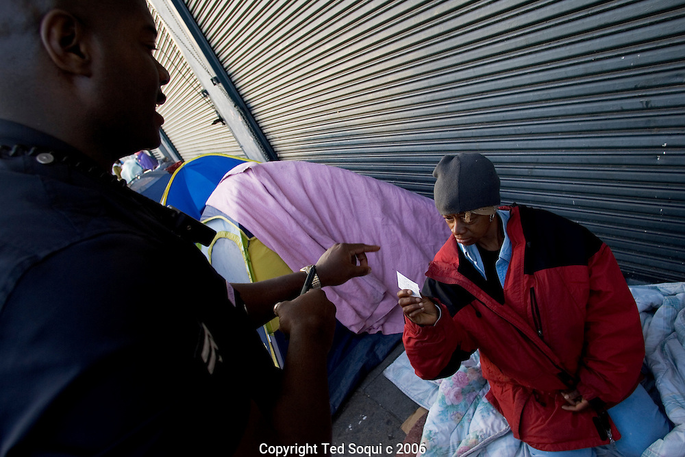 LAPD Senior Lead Officer Deon Joseph speaks to a homeless women and gives her some information to help her get off the streets of Downtown LA.