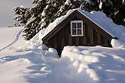 A trail leads through deep snow to the toilet outhouse adjacent to the Elfin Lakes Hut, a large shelter in Garibaldi Provincial Park, British Columbia, Canada.