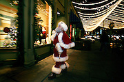 """Santa Claus peruses some of the shops of Larimer Square during the 2006Holiday season in Denver, Co. Santa Claus, also known as Saint Nicholas, Father Christmas, Kris Kringle, or simply """"Santa"""" is a legendary and historical character associated with bringing gifts on Christmas Day..(Photo by Marc Piscotty/ © 2006)"""