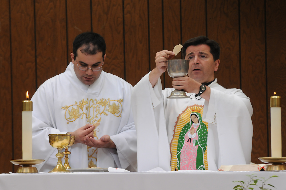Father Franco Liporace (R) leads parishioners at St. Francis of Assisi Catholic Church in worship with Assistant Pastor Ruben Rios during a weekly mass in the church gymnasium.