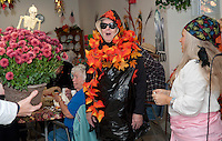 Director R. Paul Weston presented first place for best costume to Eleanor Leclerc dressed as a bag of leaves during the Laconia Senior Center's Halloween luncheon on Thursday with Program Assistant Tina Goss looking on.  (Karen Bobotas/for the Laconia Daily Sun)