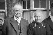 vintage elderly couple standing outside a house