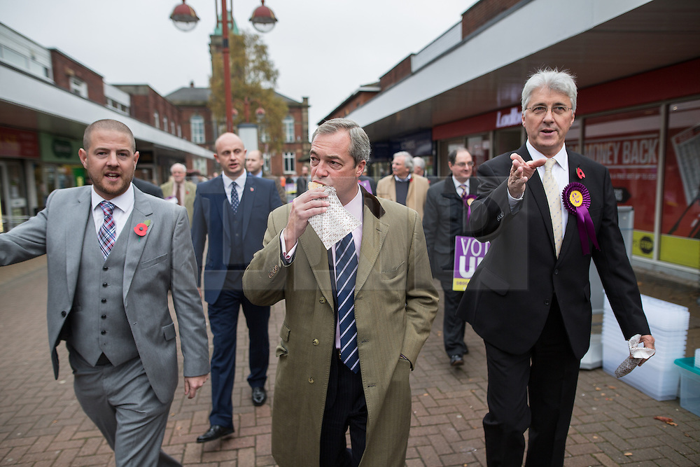 © Licensed to London News Pictures . 03/11/2015 . Oldham , UK . UKIP leader NIGEL FARAGE (c) with candidate JOHN BICKLEY (r) eating a pie in Royton Shopping Centre , at the launch of the party's campaign for the seat of Oldham West and Royton . The by-election has been triggered by the death of MP Michael Meacher . Photo credit : Joel Goodman/LNP