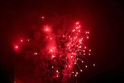 Fireworks explode in red sky