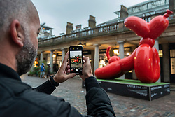 © Licensed to London News Pictures. 07/10/2021. LONDON, UK. A man photographs Stretching Balloon Dog by the artist known as Whatshisname (real name Sebastian Burdon) installed in Covent Garden. In total, four colourful balloon dogs are on display until the end of October.  The public are encouraged to take photos and post them to social media with a hashtag #castleforbluecross and Castle Fine Art will donate £1 to the Blue Cross animal welfare charity for each post..  Photo credit: Stephen Chung/LNP