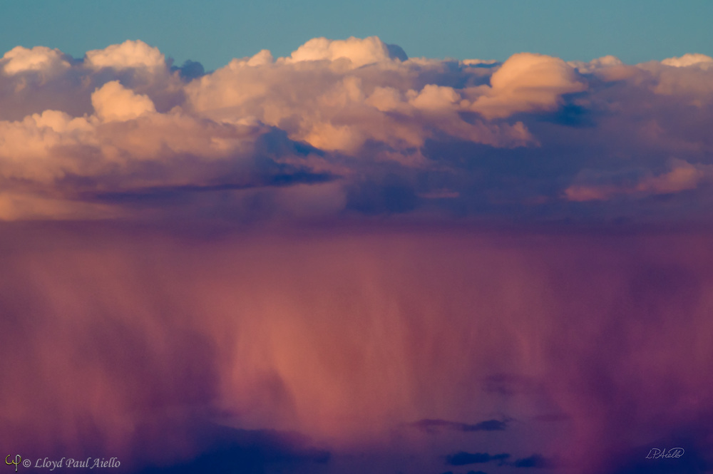 """Above the painted desert in Arizona, sheets of heavy rain glow pink at sunset beneath the white clouds of an approaching storm.  The Painted Desert encompasses over 93,500 acres, stretching for over 160 miles, and derives its name for the multitude of colors ranging from lavenders to shades of gray with vibrant reds, oranges and pink.  The area is a long expanse of badland hills and buttes which, although barren and austere, encompass a rainbow of colors due to the colorful sediments of bentonite clay and sandstone. <br /> <br /> The desert is composed of stratified layers of easily erodible siltstone, mudstone, and shale of the Triassic Chinle Formation. These fine-grained rock layers contain abundant iron and manganese compounds which provide the pigments for the various colors of the region.<br /> <br /> The Painted Desert was named by an expedition under Francisco Vázquez de Coronado on his 1540 quest to find the Seven Cities of Cibola, which he located some forty miles east of here. Discovering that the cities were not made of gold, Coronado sent an expedition to find the Colorado River for supplies. The group passed through the colorful landscape and named the area """"El Desierto Pintado"""" - The Painted Desert."""