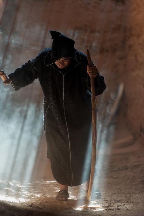 A traditional dressed Moroccan man walks inside a dusty Kasbah.