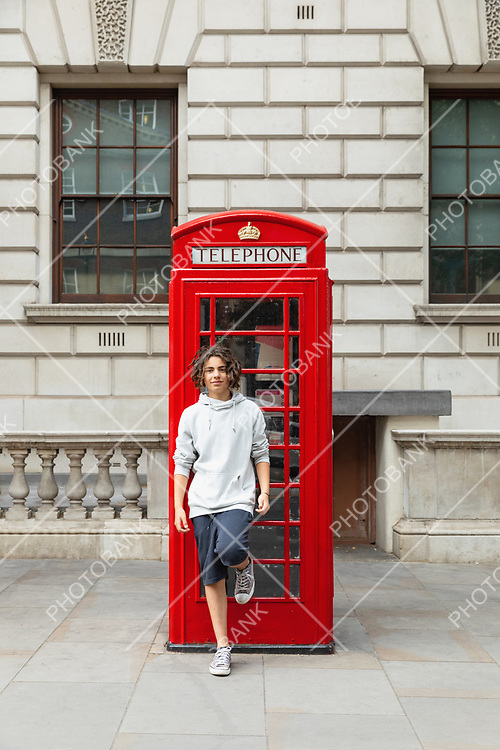 Boy stands by a telephone box in London.