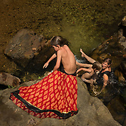 Mother and 2 sons swim in a river.