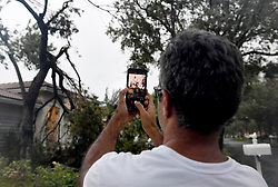 """The Vineyards in Monarch Lake resident Syed Ali takes pictures of down tree limbs in his neighbor's front yard after Hurricane Irma left the Miramar community, sparing it from major damage other than down trees, branches and mailboxes on Sunday, September 10, 2017. """"Thank God it didn't fall on either of our houses,"""" said Ali. Photo by Taimy Alvarez/Sun Sentinel/TNS/ABACAPRESS.COM"""
