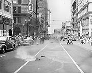 """Y-470806-01. """"Confusion. Firemen, fire trucks, hose, smoke and lots of spectators crowed SW 6th Avenue Wednesday afternoon after an electrical conduit of Pacific Power & Light blew up, shaking business district."""" SW 6th & Alder looking north. Bottom of Oregonian sign shows on left. Upper center Equitable building & sign. August 6, 1947"""