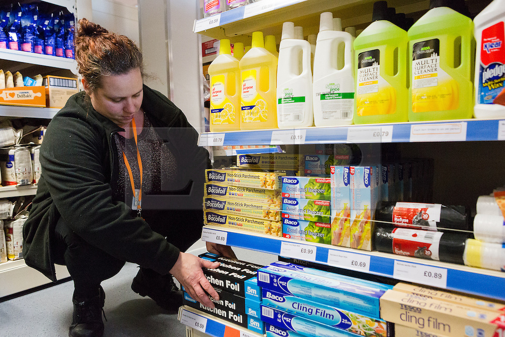 """© Licensed to London News Pictures. 19/12/2014. London, UK. A member of staff fills the shelves in the Community Shop with cleaning products. The Community Shop opened this week in Gipsy Hill, South London and is a """"social supermarket"""", which sells heavily-discounted surplus food that would otherwise be thrown away. Food is received from retail brands such as Marks & Spencer, Asda, Tesco, Innocent and Muller and many more. The shop works on a membership basis only, serving residents who are on income support and aimed at people who are in work, but low waged and for those working hard to find a job. Photo credit : Vickie Flores/LNP"""