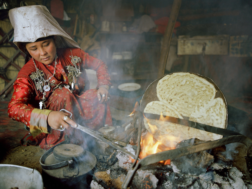 """Pegich, young wife of Er Ali Boi (married 2 years), the richest  """"sane"""" man in Pamir, bakes bread. Er Ali Boi is one of the rare Kyrgyz to spend winter in a yurt.<br /> Campment of Esh Keli.<br /> Winter expedition through the Wakhan Corridor and into the Afghan Pamir mountains, to document the life of the Afghan Kyrgyz tribe. January/February 2008. Afghanistan"""