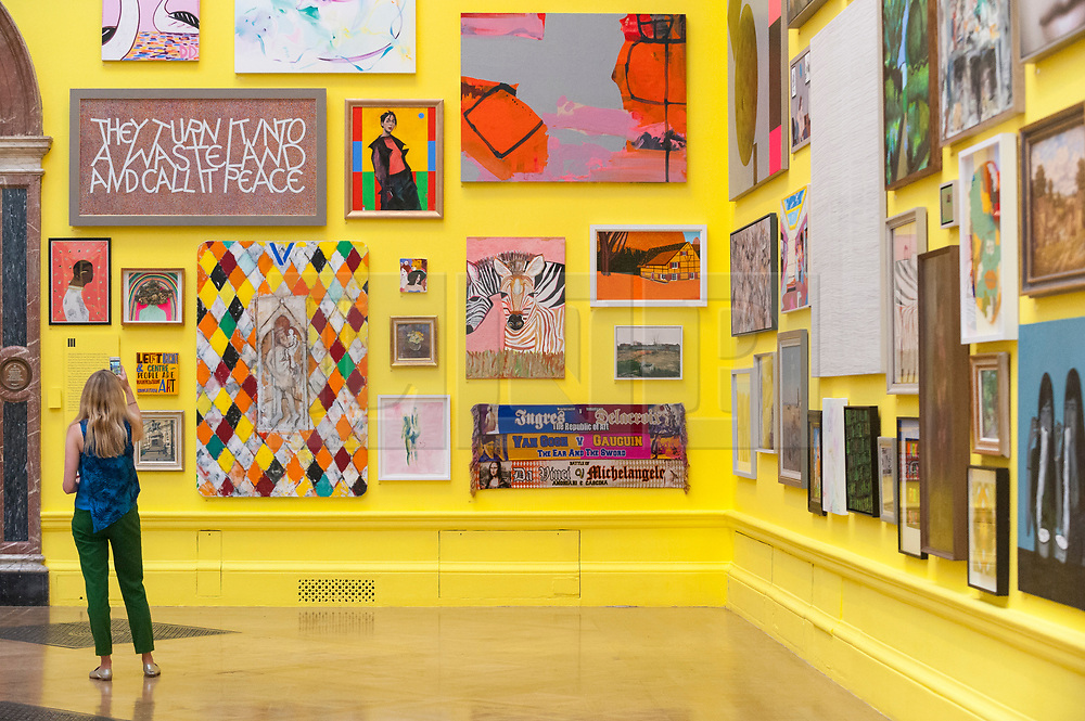 © Licensed to London News Pictures. 05/06/2018. LONDON, UK. A staff member views artworks in a vividly painted gallery at a preview of the 250th Summer Exhibition at the Royal Academy of Arts in Piccadilly, which has been co-ordinated by Grayson Perry RA this year.  Running concurrently, is The Great Spectacle, featuring highlights from the past 250 years.  Both shows run 12 June to 19 August 2018.  Photo credit: Stephen Chung/LNP