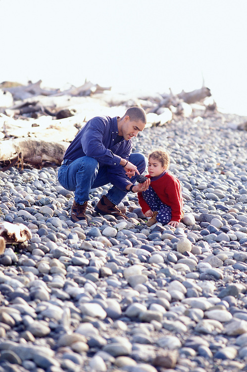 A father and daughter exploring on a rocky beach.