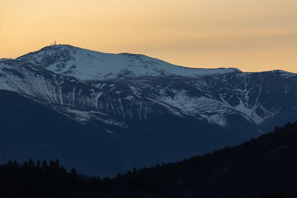 A cold evening sunset glowing behing Mount Washington.
