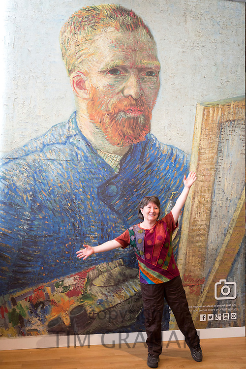 Woman posing in front of poster of self portrait of Vincent Van Gogh at the Van Gogh Museum gallery  in Amsterdam, Holland