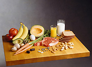 A butcher block counter with an assortment of nutritious foods representing the main food groups