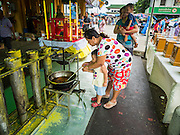 20 JULY 2015 - NONTHABURI, NONTHABURI, THAILAND:  A woman and her son put wax into a candle mold for the Rains Retreat (also called Buddhist Lent) on Nonthaburi Pier, the end of the Chao Phraya Express Boat line in Nonthaburi, a suburb of Bangkok. This is the north end of a plan to develop the Chao Phraya River riverfront. The Chao Phraya promenade is development project of parks, walkways and recreational areas on the Chao Phraya River between Pin Klao and Phra Nang Klao Bridges. The 14 kilometer long promenade will cost approximately 14 billion Baht (407 million US Dollars). The project involves the forced eviction of more than 200 communities of people who live along the river, a dozen riverfront  temples, several schools, and privately-owned piers on both sides of the Chao Phraya River. Construction is scheduled on the project is scheduled to start in early 2016. There has been very little public input on the planned redevelopment.          PHOTO BY JACK KURTZ