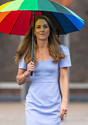 Catherine, Duchess of Cambridge, wearing an LK Bennett shift dress,  shelters from the rain under a colourful umbrella as she arrives at Kensington Palace in London to launch the Royal Foundation Centre for Early Childhood on June 18, 2021.