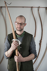 Male bow maker polishing bow in workshop, Bavaria, Germany