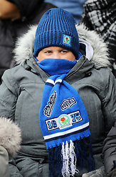 A Blackburn Rovers fan covers up from the cold conditions in the stands
