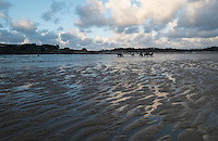 Horseback riders ride their horses in the waters of the English Channel in St Malo in northwestern France. Fluffy grey clouds float overhead, with sand shaped by the tide in the foreground.