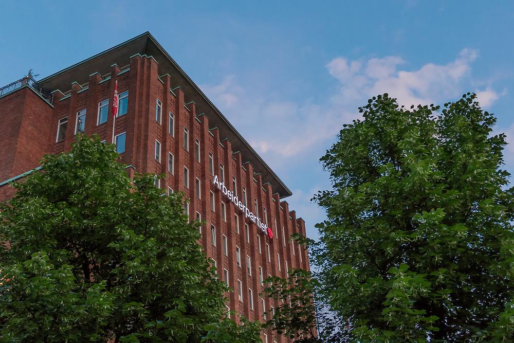 Arbeiderpartiets fasade på Youngstorget ikledd grønne trær og blå himmel.