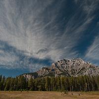Wind-blown cirrus clouds soar over Cascade Mountain in Banff National Park, Alberta, Canada.