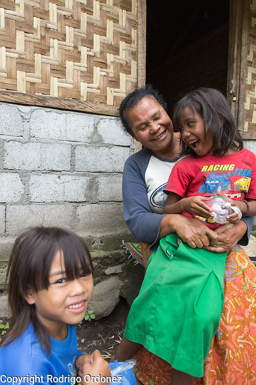 Inaq Muhamad (center), who estimates her age at 60, poses for a photograph with her granddaughters Winde, 7 (left), and Kuratulaini, 8 (right), in Sembalun Lawang, Sembalun subdistrict, East Lombok district, West Nusa Tenggara province, Indonesia. Her house was destroyed by strong winds and rains, and later reconstructed with assistance from the government in the form of construction materials.