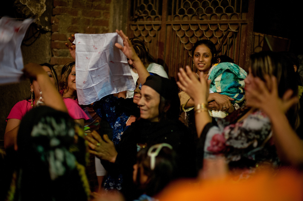 Women reveal the bloody napkin from the bridal bed, proving the girl's virginity. They then paraded the bloody napkin around the village in the back of a truck.
