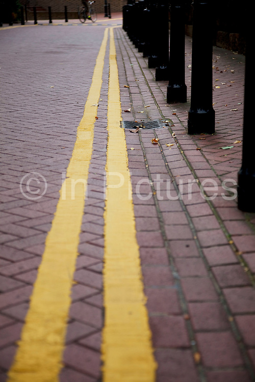 Double yellow lines painted on a street in East London. These stripes mean there is no parking allowed.