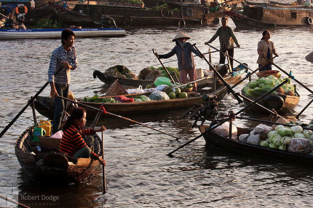 Boats laden with produce arrive at the Phong Dien floating market in the Mekong. Robert Dodge, a Washington DC photographer and writer, has been working on his Vietnam 40 Years Later project since 2005. The project has taken him throughout Vietnam, including Hanoi, Ho Chi Minh City (Saigon), Nha Trang, Mue Nie, Phan Thiet, the Mekong, Sapa, Ninh Binh and the Perfume Pagoda. His images capture scenes and people from women in conical hats planting rice along the Red River in the north to men and women working in the floating markets on the Mekong River and its tributaries. Robert's project also captures the traditions of ancient Asia in the rural markets, Buddhist Monasteries and the celebrations around Tet, the Lunar New Year. Also to be found are images of the emerging modern Vietnam, such as young people eating and drinking and embracing the fashions and music of the West. His book. Vietnam 40 Years Later, was published March 2014 by Damiani Editore of Italy.