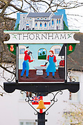 Thorn ham - one of the traditional painted village signs by traditional brick and flint wall in North Norfolk, UK