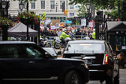 London, UK. 4 June, 2019. Protesters watch US President Donald Trump's motorcade leave Downing Street on the second day of his state visit to the UK.