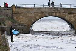 © Licensed to London News Pictures. <br /> 21/03/2015. <br /> <br /> Sandsend, North Yorkshire.<br /> <br /> A couple stand on a bridge crossing Sandsend Beck as a surfer jumps into the river to ride his board on the tidal surge at Sandsend in North Yorkshire. The exceptionally high Spring tides were created by the moon's 18-year cycle.<br /> <br /> Photo credit : Ian Forsyth/LNP