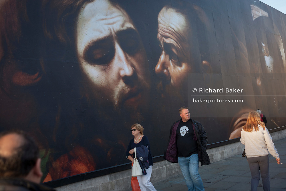A couple walk beneath the faces from The Taking of Christ (c1602) the painting of the arrest of Jesus, by Italian Baroque master Caravaggio and exhibited at the National Gallery, London.