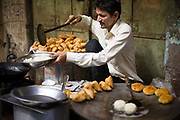 A man cooking and serving fried potato snacks on the streets of the Johari bazaar, Jaipur, India