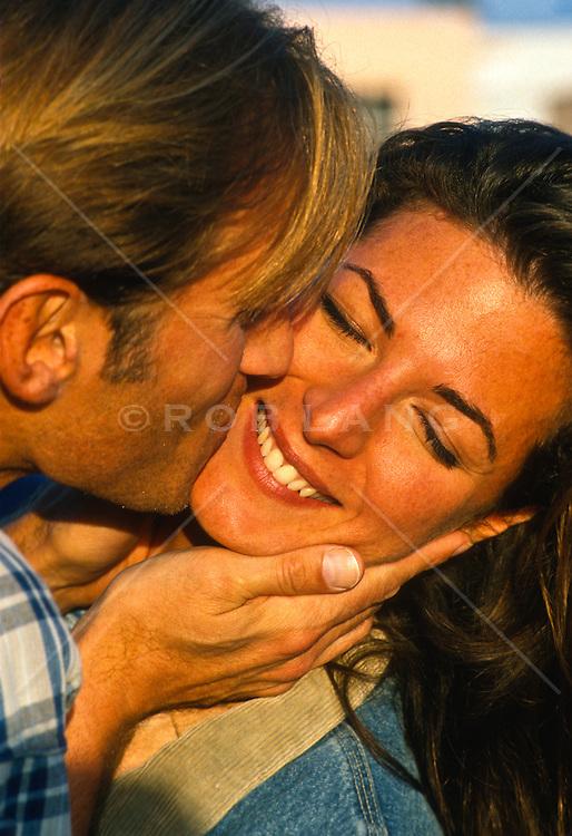 Woman enjoying a kiss on the cheek from a man