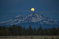 "A ""super moon"" sets over North and Middle Sister peaks near Sisters, Oregon."