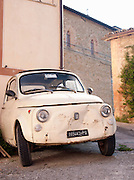 An old, Fiat car parked outside a house in the sleepy town of Solomeo in Umbria, Italy