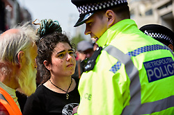 """© Licensed to London News Pictures. 17/04/2019. LONDON, UK.  Police officers request people to move on at Oxford Circus during """"London: International Rebellion"""", on day three of a protest organised by Extinction Rebellion, demanding that governments take action against climate change.  Marble Arch, Oxford Circus, Piccadilly Circus, Waterloo Bridge and Parliament Square have been blocked by activists in the last three days.  Police have issued a section 14 order requiring protesters to convene at Marble Arch only so that the protest can continue.  Photo credit: Stephen Chung/LNP"""