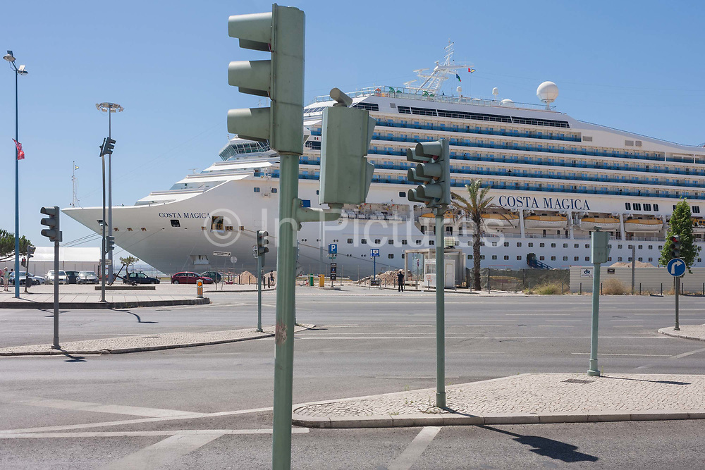 Docked at a quay and overlooked by a landscape of street lighting and posts, the cruise liner Costa Magica awaits its passengers after their excursion to the Portuguese capital, on 12th July, 2016, in Lisbon, Portugal. The ship is enormous, at 105,000 tons and carrying 2,720 passengers. <br /> Debuting in 2004 as a sister ship to Costa Fortuna, it is built on the same platform as the Destiny-class of the Carnival Cruise Lines.