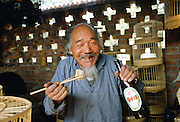 Man eating with chopsticks & drinking beer, Beijng, China