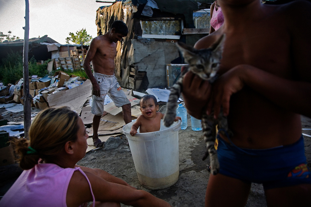 A young boy is bathed in a bucket in the central area of the Stara Gazela camp.